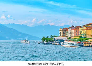 Ship arriving to Bellagio town quay at lake Como in Italy with beautiful hotels, blooming nerium oleander flowers and boats