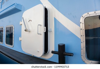 a ship or boat hatch door with blue color ship wall on harbor in view from bottom  karimun jawa indonesia