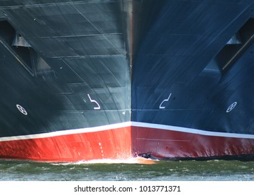 Ship Bow from dead ahead with anchors and bow wave. Ship is black and red hull showing anchors on port and starboard sides