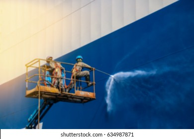 ship cleaning by jet water Work in floating dry dock the shipboard of the ship from sea vegetation before sandblast and paint blur background