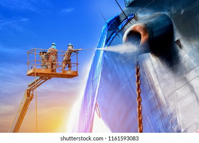 Ship cleaning by Worker two man with safety harness used pressure washer cleaning ship on Trucks have sherry piker, the success of the work in factory
