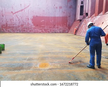 ship crew is scraping loose rust from cargo hold tanktop on a bulk carrier. perpetration for loading cargo.