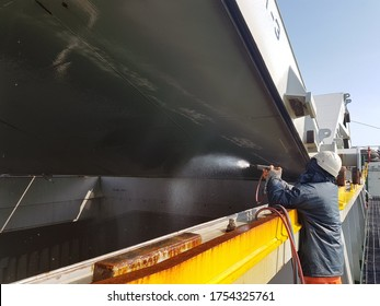 a ship crew is splashing water to wash underneath the hatch cover on bulk carrier during cargo hold cleaning operation.