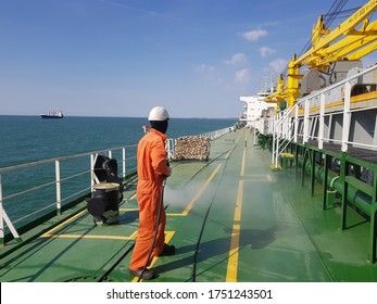 a ship crew is using high pressure washer to wash on ship main deck. Hydro blast.