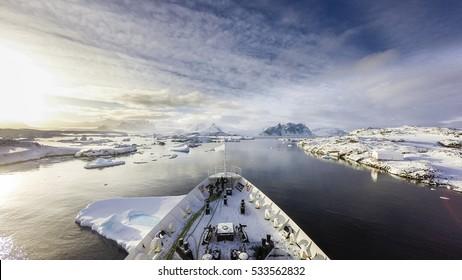 A ship cruising among icebergs  between frozen land of Antarctica and islands surrounding the main land