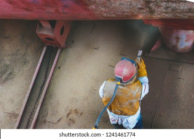 Ship in the dock. Sea tow to the dock raised out of the water for repair. Worker sandblasting knocks the paint off the ship.