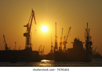 Ship in dry dock and cranes at sunset, Hamburg, Germany