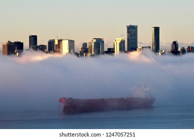 ship in fog with Vancouver city skyline in the background
