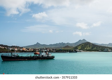 Ship in front of small town at the blue ocean coast with cloudy mountain background, Cape Verde island