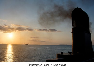 A ship funnel is exhausting black polluted smoke with deep blue sea in twilight time