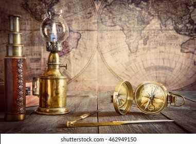Ship lamp, compass, divider and spyglass on the wood table. Travel and nautical theme grunge background. Retro style.
