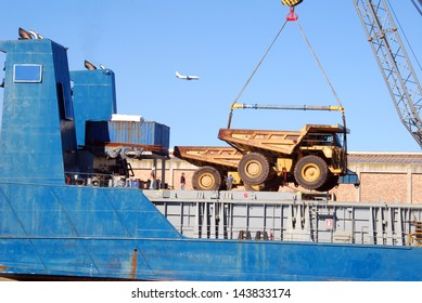 A ship loading earth moving equipment