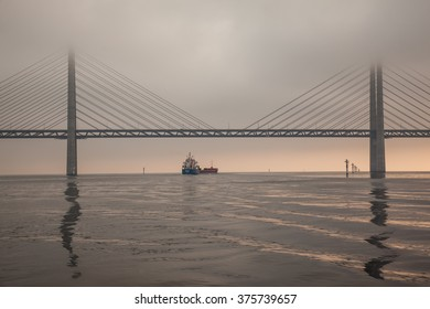Ship passing under Oresund Bridge in early morning.