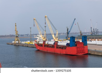 A ship in port, loaded with parts for wind turbines