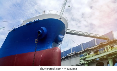 ship repair in floating dry dock sandblasting and painting before under repair in shipyard on blue sky background