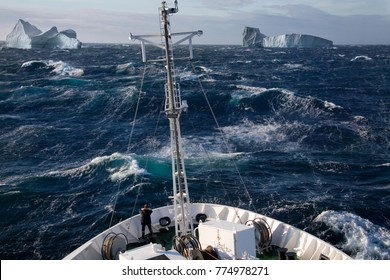 A ship rolling in heavy seas near iceburgs in Scoresbysund on the east coast of Greenland.