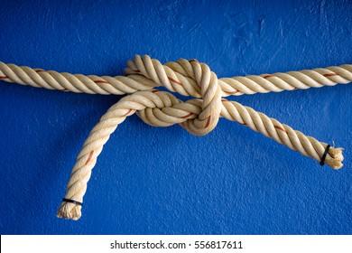 Ship rope knot on blue concrete background