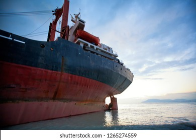 Ship is at the shore ran aground as a result of the storm. Long shipboard is on the rocks. The bow of the vessel on the shore, feed in the water.