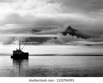 Ship sits quietly on the water while sunrise colors the clouds and mist over the Bay of Valdez in Alaska.  Sky clears in right corner of image.