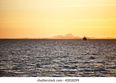 Ship in sunset and mountain silhouette
