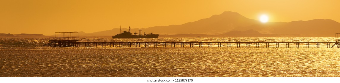 The ship swims along the sea along the pier. Large panorama of the sunset at the sea.  Egypt. Red Sea.