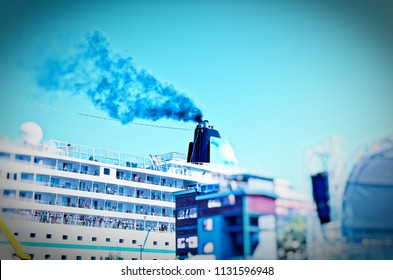 Ship that lies in a harbor with a clear plume of smoke on the chimney to illustrate the air pollution by cruise ships