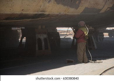 Ship under repairing on floating dry dock in shipyard.Sandblast.Sandblast