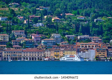 The ship of white color, several floors, moves along the coastline of the small resort town of Salo Italy on Lake Garda.