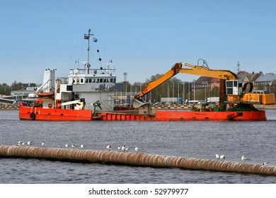 Ship with working excavator on board. Heavy machine is dredging the river of Daugava in center of port in Riga, Latvia.