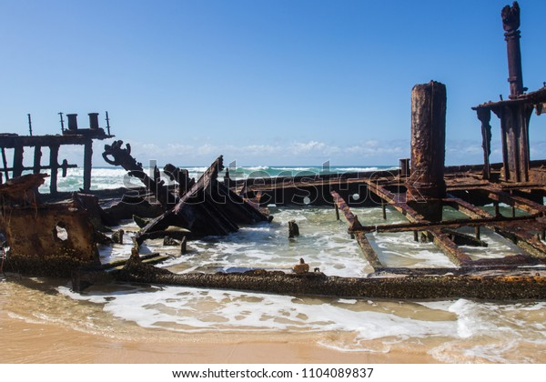 Ship wreck on the beach with blue torquoise water white wash san