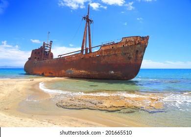 Ship wreck surrounded by sea waves on sunny Selinitsa beach, Gytheio, Greece