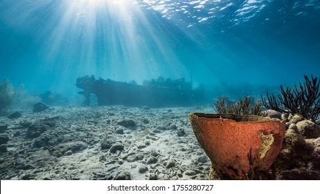"""Ship wreck """"Tugboat """" in  shallow water of coral reef in Caribbean sea / Curacao with view to surface and sunbeam"""