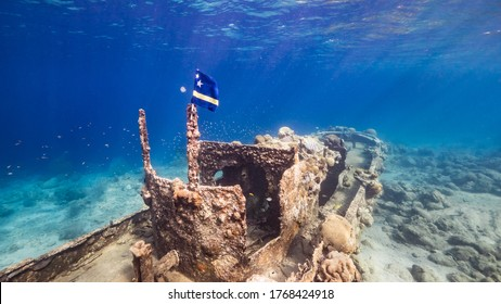 """Ship wreck """"Tugboat"""" in  shallow water of coral reef in Caribbean sea with  Curacao Flag, view to surface and sunbeams"""