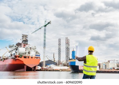 Shipbuilding engineer checking documents and plans of construction at the dockside in a port. Wearing safety helmet and yellow vest, holding folded papers.