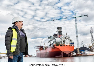 Shipbuilding engineer stands at the dockside in a port. Wearing safety helmet and yellow vest. Shipbuilding industry.