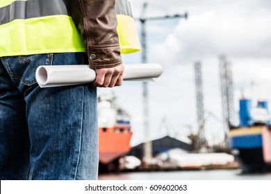 Shipbuilding engineer stands at the dockside in a port. Man is holding construction documents. Shipbuilding industry