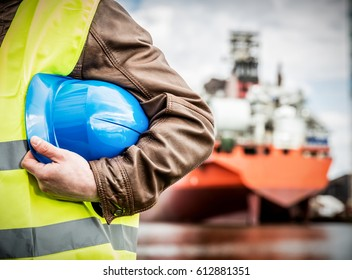 Shipbuilding engineer stands at the dockside in a port. Man is holding a safety helmet, close-up.. Shipbuilding industry