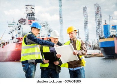Shipbuilding engineers introducing new solution in a shipyard. All men wearing safety helmets and yellow vests. Shipbuilding industry.