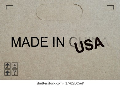 Shipment box with words 'Made in USA' replacing the fading word China. Concept for American government bringing manufacturing jobs back to US and decouple from China. America vs Chinese conflict.