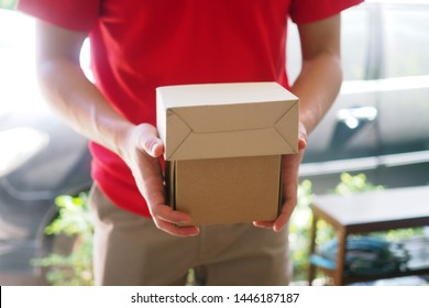 The shipper in the blue suit holds a brown box standing in front of the customer's house. Free shipping for online shopping and express delivery