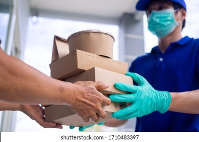 The shipper wears a mask and gloves, delivery food to the home of the online buyer. stay at home reduce the spread of the covid-19 virus. The sender has a service to deliver products or food quickly