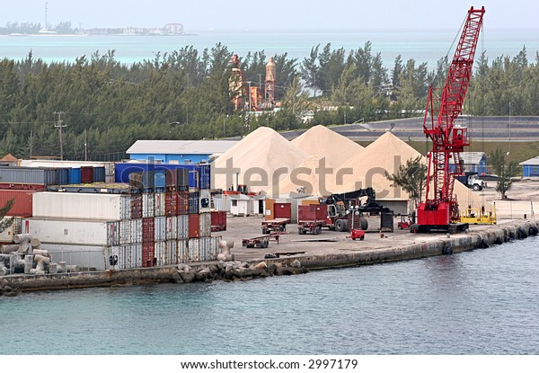 Shipping area on a bay with freight containers and sand