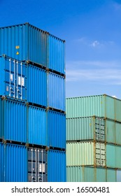 shipping cargo containers stacked under a blue sky at freight terminal