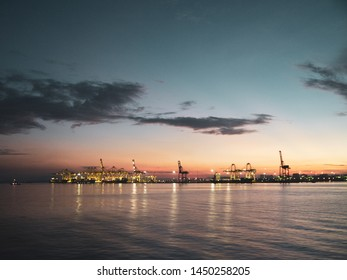 Shipping cranes at a port by the sea looking like metal giraffes during sunrise or sunset