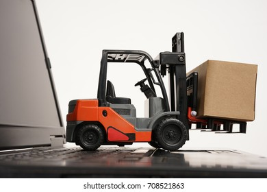 Shipping, delivery logistics technology business industrial forklift and laptop isolated on white background. Concept of delivering, shipping or logistics. Forklift on laptop keyboard