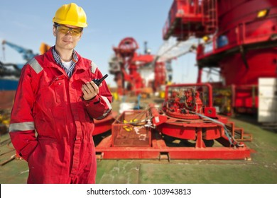 Shipping engineer with a cb-radio on the deck of a large industrial vessel, smiling into the camera on a bright sunny day