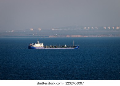 Shipping in Kerch Strait of Black sea of Azov sea. Oil tanker river-sea and huge tanks with fuel on shore (Taman), ship traffic, cabotage. Marine transportation of petroleum products, oil terminal