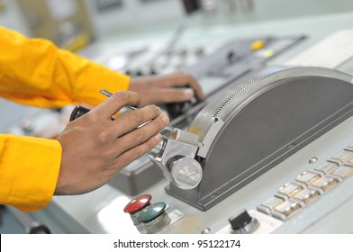 Shipping officer controlling shipping vessel at engine room.