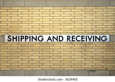 "A ""Shipping and Receiving"" sign on the yellow brick wall of a large urban building"