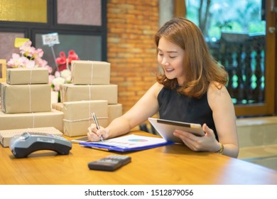 Shipping shopping online with tablets ,young start up small business owner writing address on cardboard box at workplace.entrepreneur SME or freelance Asian woman working packing flower in box at home